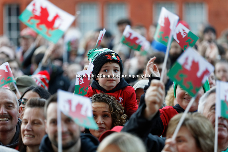 A young rugby fan looks on as Wales flags are waved around him during the Celebration for Wales Six Nations Win at the National Assembly for Wales, Cardiff Bay, Wales, UK. Monday 18 March 2019