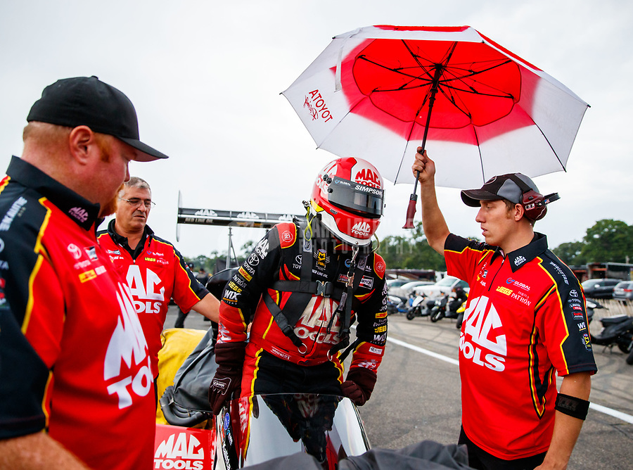 Aug 18, 2017; Brainerd, MN, USA; NHRA top fuel driver Doug Kalitta has an umbrella held over him by a crew member during a rain delay to qualifying for the Lucas Oil Nationals at Brainerd International Raceway. Mandatory Credit: Mark J. Rebilas-USA TODAY Sports