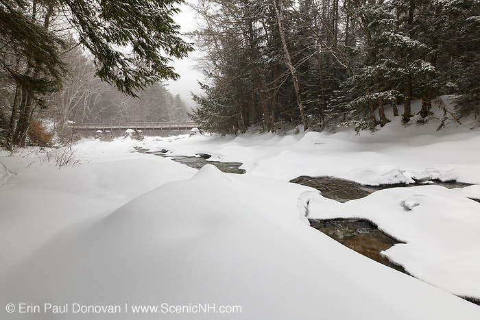 Looking downstream at the Franconia Brook foot bridge in Lincoln, New Hampshire during a winter snow storm. Hikers enter into the Pemigewasset Wilderness on the left hand side of this bridge. The abutments from trestle No. 7, which serviced the Upper East Branch of the old the East Branch & Lincoln Railroad (1893-1948), are used to support the bridge.