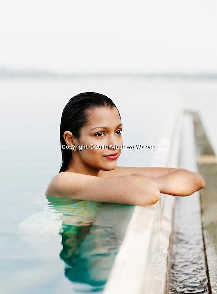 Woman in Pool at Heritance Kandalama Hotel, Dambulla, Sri Lanka.  A woman bathes in the Infinity Pool, one of three swimming pools at Heritance Kandalama Hotel, designed by Sri Lankan architect Geoffrey Bawa. November14,2008. Dambulla, Sri Lanka.
