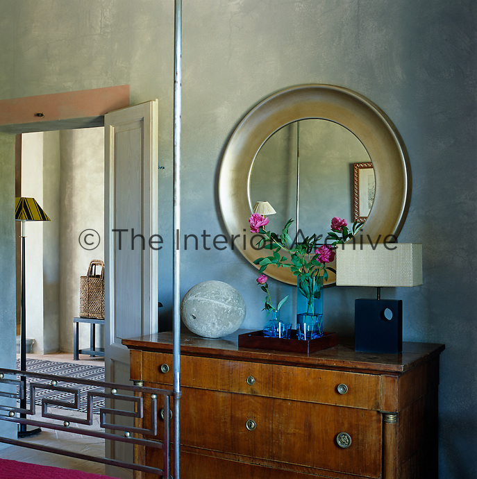 A circular mirror and an antique chest of drawers in a guest bedroom