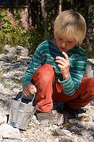 Kinder suchen auf der Abraumhalde eines Mineralien-Bergwerkes nach Mineralien und Steinen