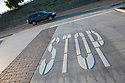 A tilted view of a 'STOP' road marking at an intersection, a sports utility vehicle (SUV) passing by in the background.  Mountain View, California, USA