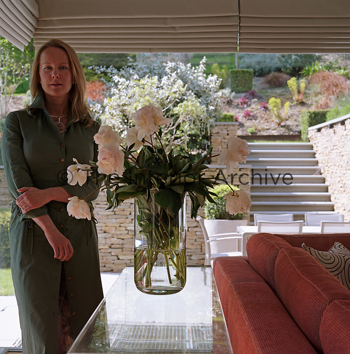 Art dealer and curator Anna Belayeva stands beside a vase filled with white peonies in the living room of her home