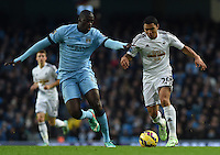 Picture by Howard Roe/AHPIX.com. Football, Barclays Premier League; <br /> Manchester City v Swansea City ;22/11/2014 KO 3.00 pm <br /> Etihad Stadium;<br /> copyright picture;Howard Roe;07973 739229<br /> Swansea's    Jefferson Montero tussles with   Manchester's    Yaya Toure