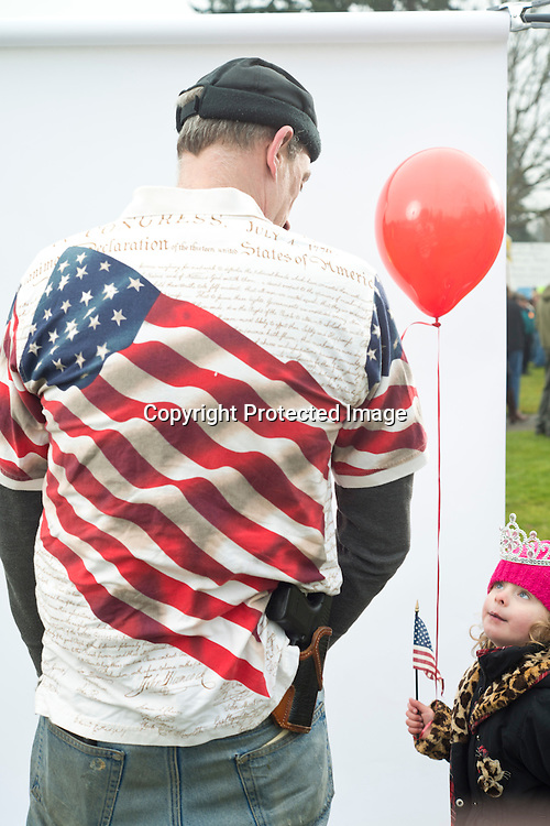 "Gary Ehrheart, of Anacortes, speaks with his daughter Ellamina, 4, while attending the Guns Across America rally that drew about 1,500 people to the Washington State Capitol in Olympia Saturday, Jan. 19, 2013.  ""I own guns for my enjoyment, for my protection and for the protection of our liberty,"" Ehrheart said while wearing a constitution shirt he paid $2.99 for at a local Value Village thrift store recently. Photo by Daniel Berman/www.bermanphotos.com."