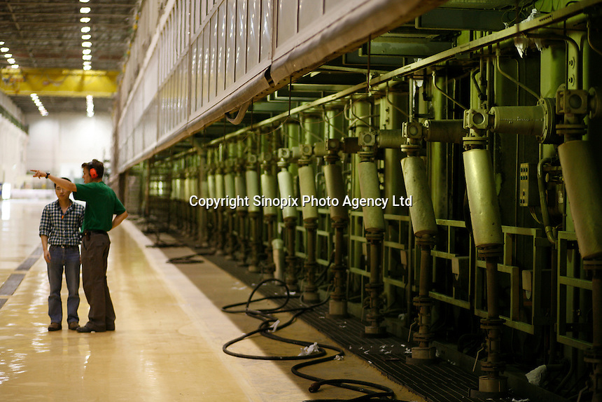 Two workers standing beside one of the gigantic paper machines at UPM Changshu Paper Plant in Changshu, China. At the price tag of 1 billion USD (830 million Euros), he UPM plant is the largest single investment made by a Finnish company in China..18 May 2006