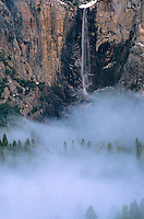 799458542 winter fog shrouded the valley below bridalveil falls as the waterfall cascades down the side of the mountain in yosemite national park in california