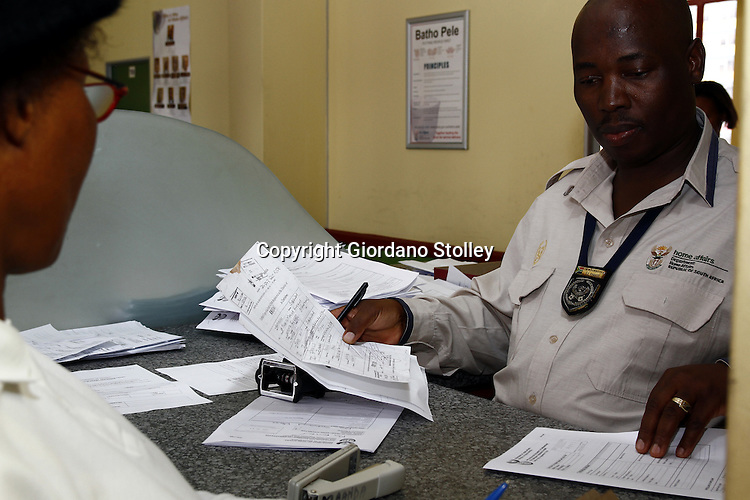 JOHANNESBURG - 31 December 2010 - A Department of Home Affairs official at the department's Harrison Street Office assists an undocumented Zimbabwean national to apply for residency permits -- APP/Allied Picture Press