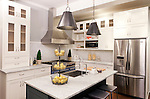 Homeowner's Peggy Gilmore and Kevin Wood's new kitchen features marble countertops and backplash, new appliances and range hood, a kitchen island with a farmer sink, after transformation by the crew of DIY Network's original series Kitchen Crashers.