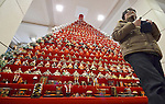 """February 17, 2013, Konosu, Japan - A visitor walks away from Girls' Fewstival ornamental dolls displayed on the red-carpeted platform in a huge pyramid shape at the lobby of Konosu city hall, north of Tokyo, on Sunday, February 17, 2013. The dolls numbered 18,000 represent emperor, empress, attendants and musicians in the ancient Imperial court. The city of Konosu, situated some 40 km north of Tokyo, is known as """" the doll town"""" for a number of factories manufacturing Japanese dolls. Japanese tradition calls upon families with daughters for putting out dolls for the Girls Day on March 3 with the hopes that they grow up healthy and happily. (Photo by Natsuki Sakai/AFLO) AYF -mis-."""