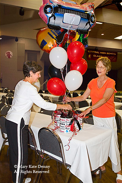 Two  female alumnas design balloons,basket and mylar car balloon for table decoration at the 50th high school reunion