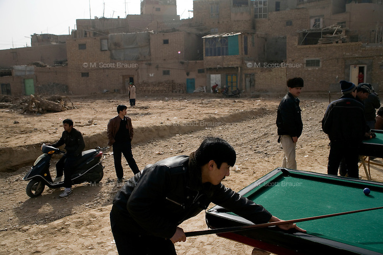 People play pool in an area of the Old City where houses once stood in Kashgar, Xinjiang, China.