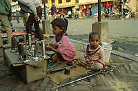 Young girls repairing and selling torches along the road