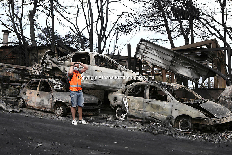 Pictured: A volunteer prepares in the aftermath of the forest fire which has claimed dozens of lives in the Mati area of Rafina, Greece. Tuesday 24 July 2018<br /> Re: Deaths caused by wild forest fires throughout Greece.