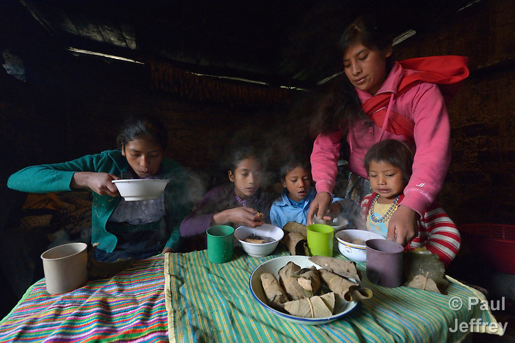 Children eat breakfast at their home in Tuixcajchis, a small Mam-speaking Maya village in Comitancillo, Guatemala. They are, from left, Griselda, 13; Lidia, 11; Elder, 6; and Nyda Diaz Vasquez, 3. They are being served by their older sister, Maria Elvira, 18.