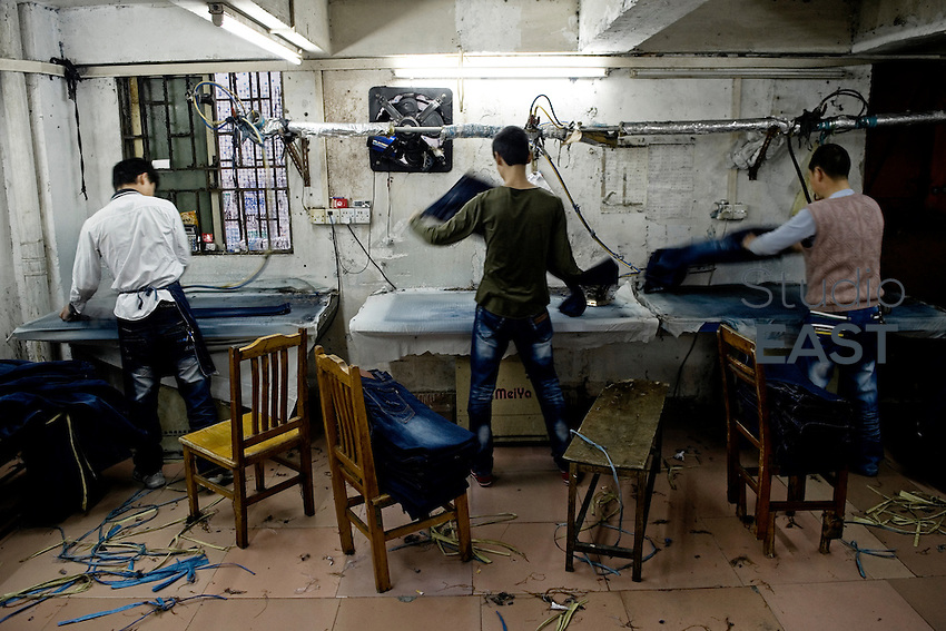 Workers iron newly-manufactured blue jeans in a little workshop by the street in Xintang, Guangdong province, China, on February 10, 2012. Photo by Lucas Schifres/Pictobank