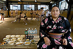 Takeuchi Masato, a professional sumo wrestler whose ring name is Miyabiyama (meaning ?Graceful Mountain?), with his day's worth of food in the team's practice ring in Nagoya, Japan. (From the book What I Eat: Around the World in 80 Diets.) The caloric value of his typical day's worth of food in June was 3500 kcals. He is 29 years of age;  6 feet, 2 inches tall; and 400 pounds. Miyabiyama's stable runs through a brutal three-hour practice?sweaty, combative, and silent. Miyabiyama wears the white mawashi (at left) denoting his sekitori status during practice. His food may not look like much for a 400-pound man, but it's enough to maintain his weight and give him energy for the ring. When he isn't in intensive training before a match, he is wined and dined nightly by sponsors. The portrait above is a composite, taken on two consecutive days: the sumo association wouldn't allow Miyabiyama to be photographed during practice.  Miyabiyama (His ring name?Masato Takeuchi is his given name), 29, a sumo wrestler with the Musashigawa Beya of Tokyo is that stable's (beya's) premier wrestler and is currently at the sekiwake (junior champion) level.  He is one of the largest of the Japanese sumos and would probably have moved up even further in the ranks had he not suffered a severe shoulder injury. He is only just now returning to matches. Sumos cook and eat chanko nabe?a stew pot of vegetable and meat or fish at nearly every meal. It  is eaten with copious amounts of rice and numerous side dishes. Miyabiyama eats now to maintain his weight rather than to gain it, unlike the younger less gargantuan wrestlers in his stable who are eating a lot to pack on weight. Although he is wined and dined by the sponsors of his team, during the period of these photographs he was training for the next matches in Nagoya, and  therefore he wasn't eating out in restaurants nor drinking alcohol.  MODEL RELEASED.