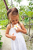 INDONESIA, Mentawai Islands, Kandui Resort,  young girl holding a plumeria flower, looking down