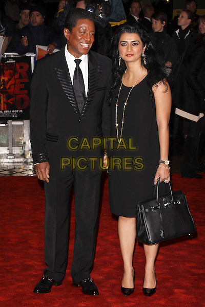 "JERMAINE  JACKSON  & HALIMA RASHID .""Red"" UK film premiere, Royal Festival Hall, Southbank Centre, London, England, UK, 19th October 2010. .full length husband wife Hermes birkin bag dress black suit tie smiling white shirt married couple holding hands CCAP/AH.©Adam Houghton/Capital Pictures."
