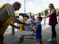 NWA Democrat-Gazette/CHARLIE KAIJO Hack Merryman, 4, with mother, Buffie Merryman of Fayetteville, (from right) make a donation to Bob Schmitz during a Tootsie Roll drive, Friday, October 5, 2018 at Walmart in Rogers.<br /><br />The Knights of Columbus is kicking off their annual tootsie rool drive Friday. The fundraiser runs through Oct. 13. They hand out Tootsie Rolls and accept donations, similar to the VFW poppy campaign.