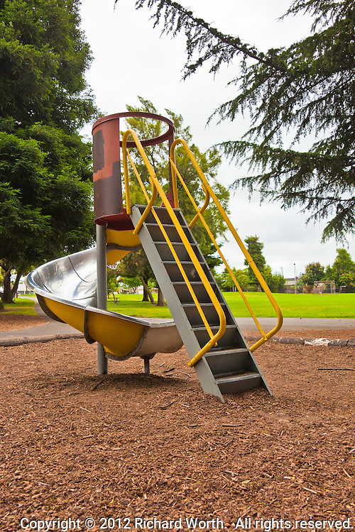Steps lead up a yellow and red spiral playground slide with the green grass of an urban park in the background.