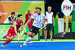 Tanguy Cosyns #32 of Belgium carries the ball while Juan Gilardi #4 of Argentina covers during Argentina vs Belgium  in the men's gold medal game at the Rio 2016 Olympics at the Olympic Hockey Centre in Rio de Janeiro, Brazil.