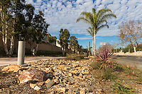 The rocky landscaping along the Harbor Boulevard Cornerstone Bike Trail in Costa Mesa, California under a blue sky dotted with small clouds.  The rocks flow along the trail like a dry streambed, framed with other plants.  The landscape architecture work on the project was done by David Volz Design.