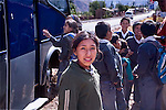 Peruvian elementary age girl in jacket waits with school boys and girls in uniforms at bus stop in Peru in mountains