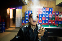ROMANIA / Maramures / Budesti / 21.10.2006 ..Vasilya, 16, smokes in an empty village bar on a Saturday night. In recent years, Budesti, like other villages in Maramures, has seen the majority of its young people leave to work abroad in Western Europe. ..© Davin Ellicson / Anzenberger