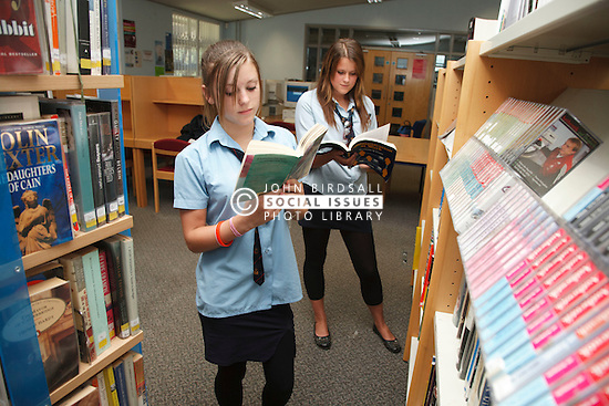 Pupils in school library looking at books.