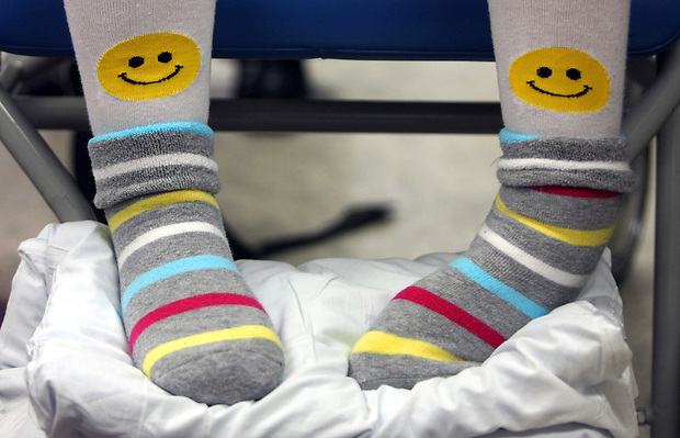 Elizabeth wears smiley-faced socks.  Her parents, Barb and Mike, have surrounded Elizabeth with positivity since she suffered a severe brain injury.