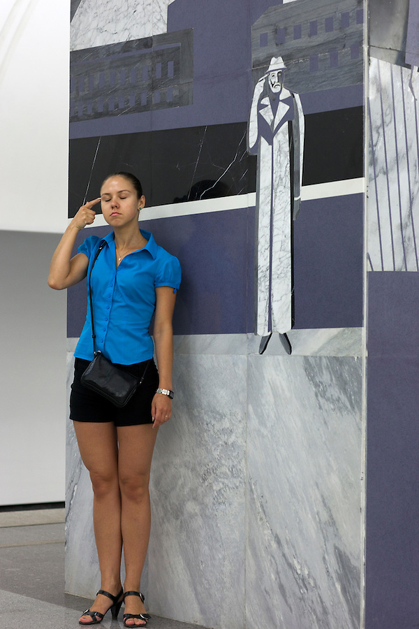 "Moscow, Russia, 20/06/2010..A girl poses beside a mural depicting Svidrigailov's suicide in Crime & Punishment at the just-opened Dostoevsky metro station, the newest in Moscow's underground metro system. The station's opening was delayed by several weeks after psychiatrists claimed the gloomy and violent images in murals depicting scenes from Dostoevsky's novels would make the station a ""mecca for suicides""."