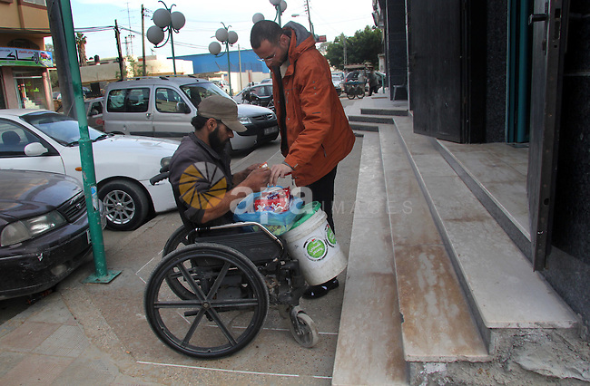 "Palestinian Ibrahim Abu Thuraya, 28 years old, sells sweets in Gaza city on 16 January 2013. Thuraya was struck by an israeli artillery shell. He lost both his legs and one of his eyes during the three-week armed conflict in the Gaza Strip between Israel and Palestinian militants. The conflict called ""Operation Cast Lead"" resulted in around 1400 Palestinian deaths. Photo by Ezz al-Zanoon"