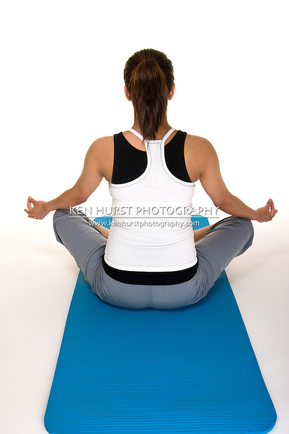 Beautiful young, Hispanic woman meditating in a yoga fitness workout to keep herself physically fit during her pregnancy.  Model is sitting with her back toward the camera. Shot on white background.