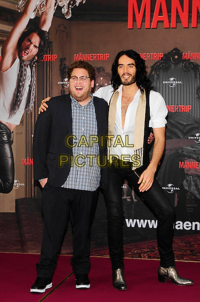 """JONAH HILL & RUSSEL BRAND.Photocall for """"Get Him To The Greek"""", Hotel Adlon, Berlin, Germany..June 25th, 2010.full length black trousers jeans denim blue check shirt gold boots shoes white shirt beige scarf tights beard facial hair glasses arm over shoulder unbuttoned .CAP/PPG/NK.©Norbert Kesten/People Picture/Capital Pictures"""