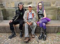 Oudere man zit op een bankje tussen twee gothics,  tijdens het Summer Darkness Fesival in Utrecht