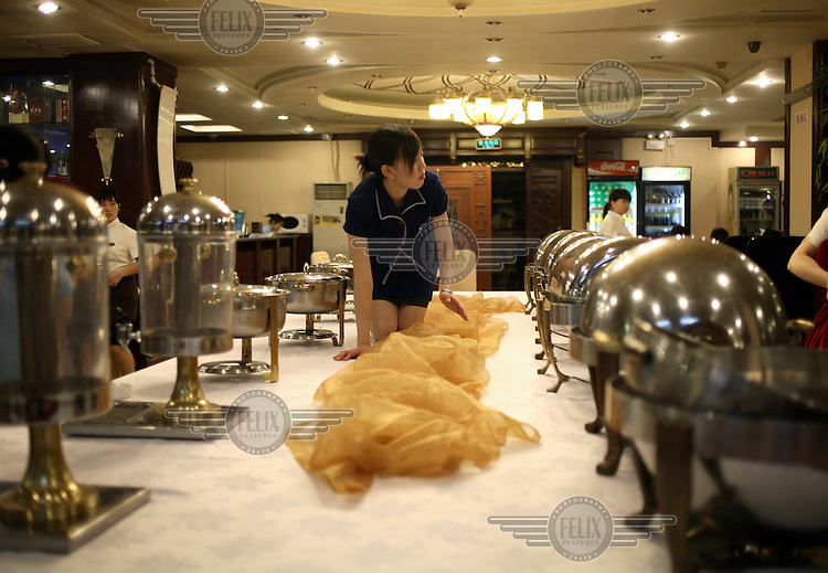 A waitress sets up a table at a restaurant in Beijing.
