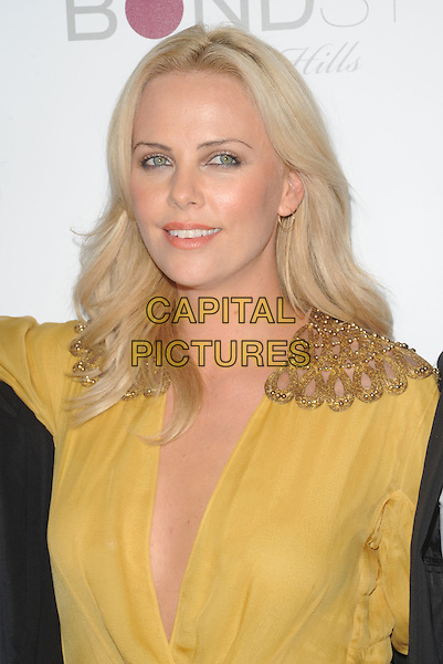 CHARLIZE THERON.The Burning Plain Premiere held at  BOND STREET at Thompson Beverly Hills in Beverly Hills, California, USA..September 14th, 2009                                                                   .half length yellow sheer gold shoulder pads epaulettes plunging neckline cleavage headshot portrait .CAP/DVS.©Debbie VanStory/Capital Pictures.