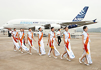 Ceremonial hostesses walks past a Airbus A380 jumbo jet at the 2008 China International Aerospace and Aviation Exhibition in Zhuhai, China. The Airshow is the only international aerospace trade show in China that is endorsed by the Chinese central government. It features the display of real-size products, trade talks, technological exchange and flying display..