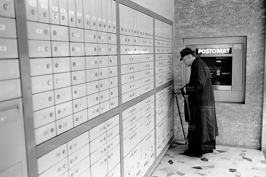 Switzerland. Canton Ticino. Massagno. Post office boxes. A catholic parish priest collects his mail at the P.O. box. Clerical dress. A postomat cash machine is on the wall. Post machine and cash point. Massagno is 5 km distant from Lugano © 1999 Didier Ruef