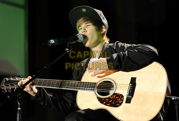 JUSTIN BIEBER.Justin Bieber performs a free holiday concert at Citadel Outlets in Los Angeles, California, USA..December 14th, 2009.half length stage concert live gig performance music black jacket guitar hat singing.CAP/RKE/DVS.©DVS/RockinExposures/Capital Pictures.