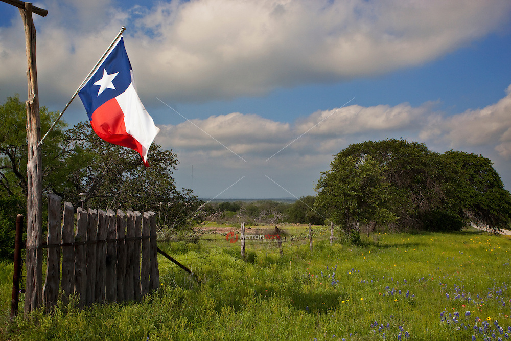 A Texas Flag proudly flies from the gate entrance at a Texas Hill Country Ranch