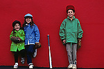 Brother and sisters posing after game, smiling, hamming it up in front of camera in front of red wall,