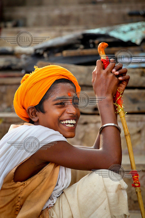A young young sadhu laughing.