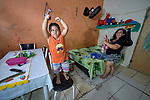 Samuel Alves da Silva, 3, poses as the Incredible Hulk in the one-room apartment he shares with his mother, Maria Ioni Brandowauvis, in Manaus, Brazil. The indigenous family migrated to the city in 2018, joining with other poor families to take over an unoccupied building--the Casa do Estudante--in the city center.<br /> <br /> Written parental consent obtained.