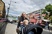 A mother uses a mobile phone while pushing her children in a pushchair in Camden Town, London.