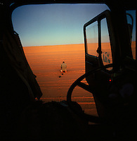Sahara desert, Libya-Chad, November/December 2004..Every week, a convoy of 40 privately owned Libyan trucks loaded by the WFP with about 1000 metric tons of western food aid cross 2500 km of deep desert across Libya and Chad to reach more than 200 000 refugees from Darfur in camps near the Sudanese border. Mashalla stops the truck for his evening prayer.
