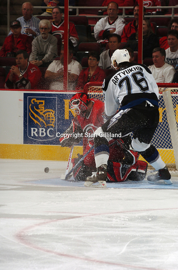 Carolina Hurricanes' goaltender Martin Gerber makes a save while the Tampa Bay Lightning's Evgeny Artyukhin watches from the crease Thursday, Sep. 22, 2005 in Raleigh, NC. Carolina won 5-2.