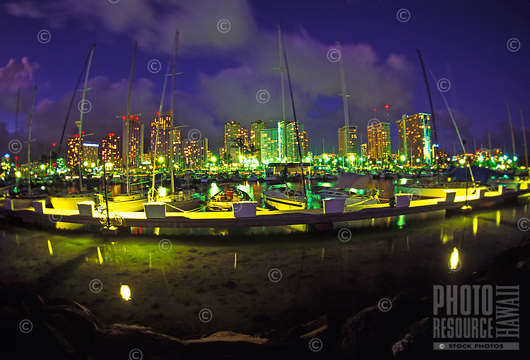 A view of Honolulu from the harbor at night with the lights illuminating the city